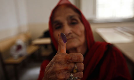 A voter displays her inked thumb after marking her ballot paper at a polling station in Karachi.